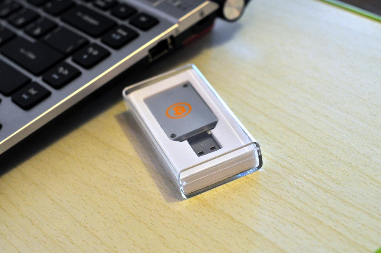 Фотография ASIC-майнера Block Erupter USB рядом с ноутбуком