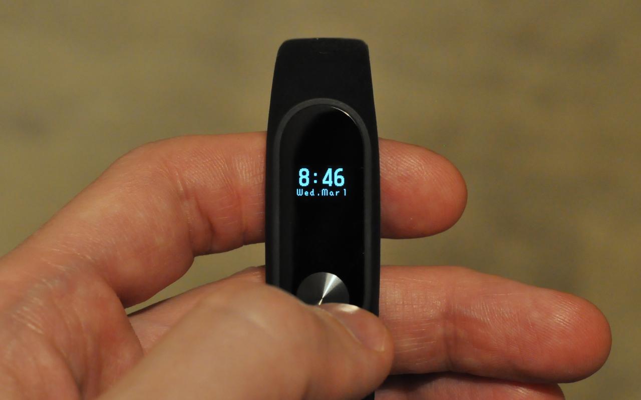 Фотография экрана Mi Band 2, где показаны часы и дата